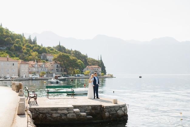 Państwo młodzi stoją tyłem do siebie na molo w zatoce kotorskiej