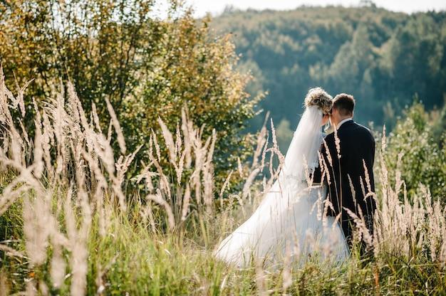 Państwo młodzi stoją w terenie po ceremonii ślubnej.