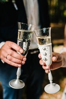 Państwo młodzi trzymają kieliszek szampana i stają na naturze podczas ceremonii ślubnej. ścieśniać. toast.