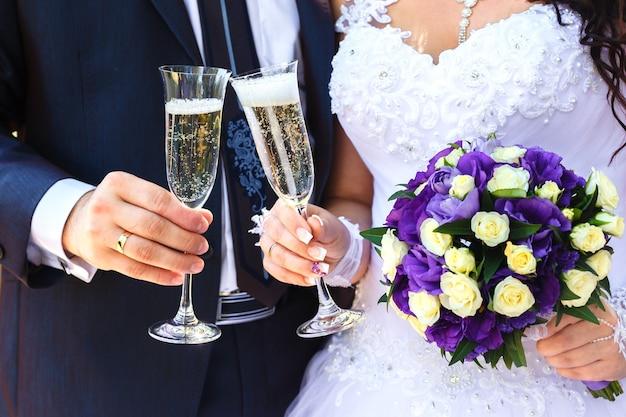 Państwo młodzi trzymają kieliszki do szampana i bukiet ślubny z biało-fioletowych kwiatów