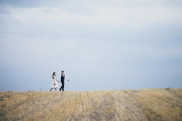 Państwo młodzi trzymają się za ręce, przytulają i spacerują po parku.