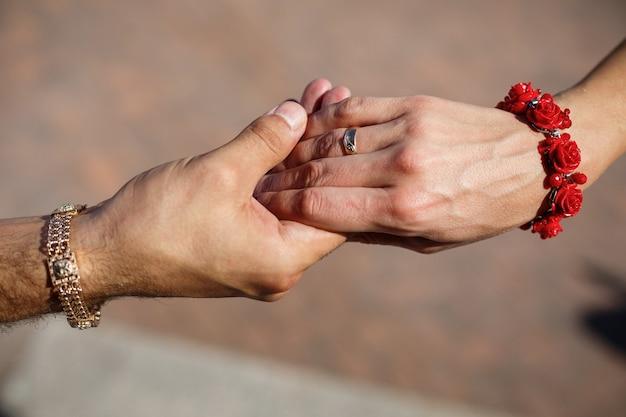 Państwo młodzi trzymają się za ręce w dniu ślubu