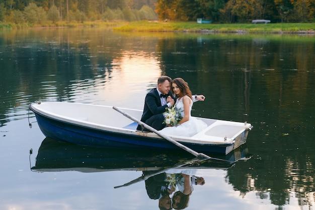 Państwo młodzi w łodzi wiosłowej na jeziorze o zachodzie słońca