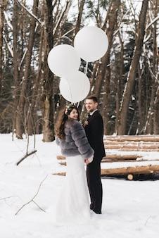 Państwo młodzi wśród śnieżnego krajobrazu z dużymi białymi balonami