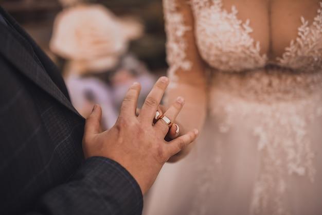 Państwo młodzi wymieniają się pierścionkami. mężczyzna wkłada obrączkę na rękę kobiety