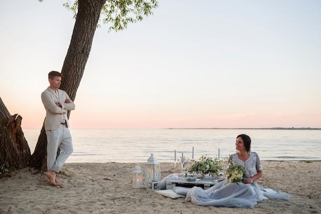 Państwo młodzi z bukietem ślubnym patrzą na siebie na plaży o zachodzie słońca