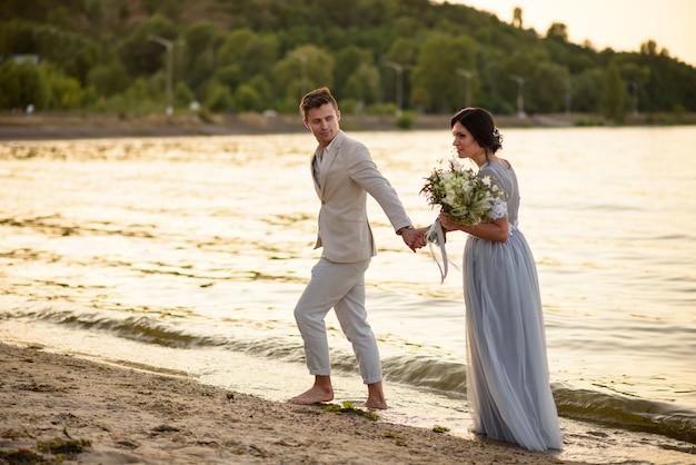 Państwo młodzi z bukietem ślubnym spacerują po plaży o zachodzie słońca
