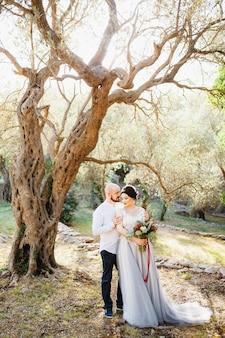 Państwo młodzi z bukietem stoją przytuleni wśród drzew w gaju oliwnym