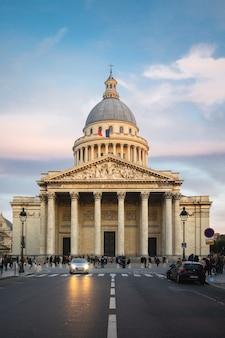 Panteon otoczony ludźmi pod zachmurzonym niebem podczas zachodu słońca w paryżu we francji