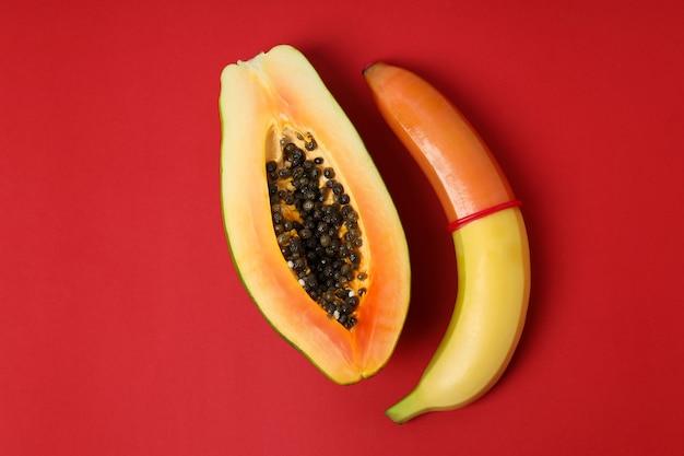 Papaja i banan z prezerwatywą na czerwonym tle