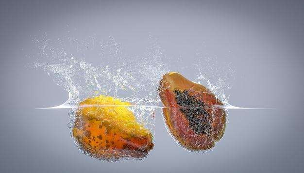 Papaja, która wpada do wody i tworzy plamy.