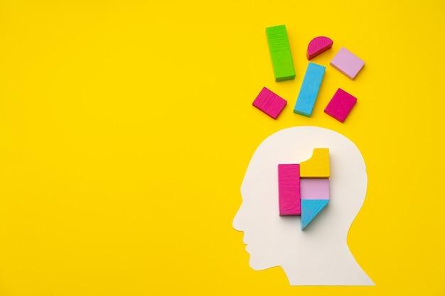 Papercut głowa sylwetka z kawałkami konstruktora zabawki na żółtym tle