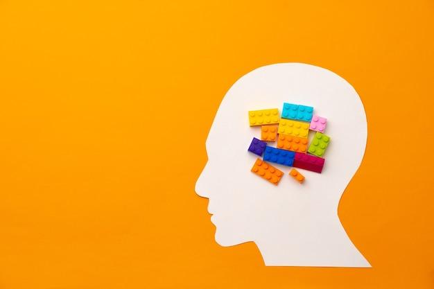 Papercut sylwetka głowy z kawałkami konstruktora zabawki na żółtej powierzchni