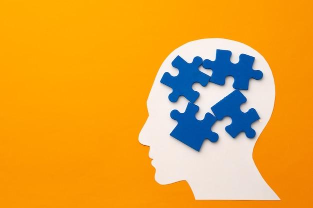 Papercut sylwetka głowy z puzzlami na żółtej powierzchni