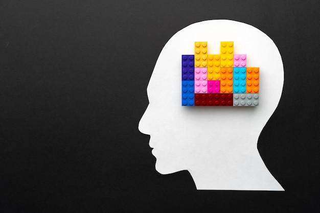 Papercut sylwetka ludzkiej głowy z kolorowymi kawałkami konstruktora