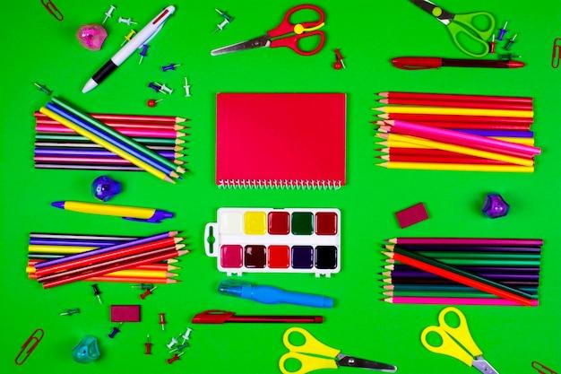 Papeteria do szkoły i biura w różnych kolorach leżą na zielonym tle.