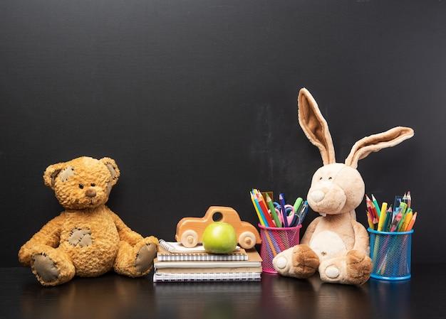 Papeteria i brązowy miś siedzi na powierzchni pustej czarnej tablicy kredowej, koncepcja z powrotem do szkoły