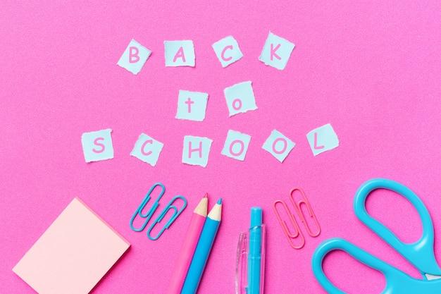 Papeteria i napis z powrotem do szkoły, różowe tło
