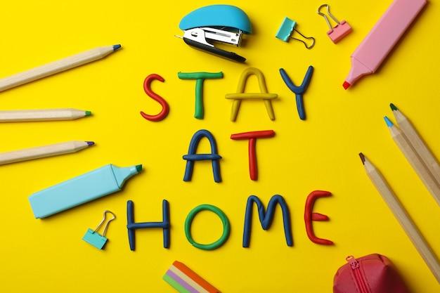 Papeteria i zostań w domu z plasteliny na żółtej powierzchni