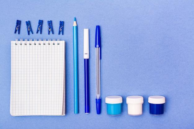 Papeteria - otwarty notatnik, ołówek, długopis, flamaster, gwasz i klipsy niebieskie tło