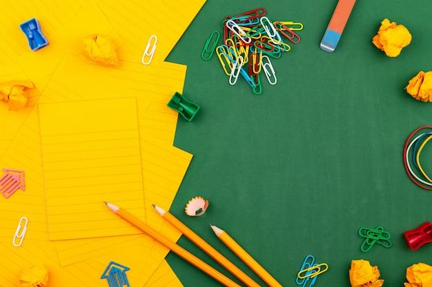 Papeteria szkolna i pomarańczowy arkusz papieru leżą na zielonej tablicy szkolnej tworząc ramkę dla tekstu. w pobliżu ołówka i pomiętych stron. skopiuj miejsce mieszkanie leżał widok z góry koncepcja edukacja