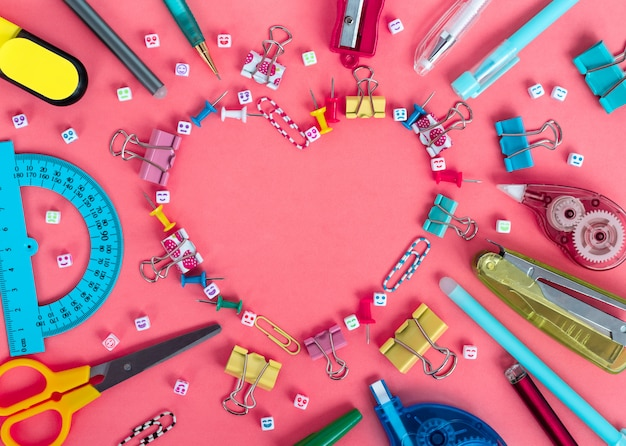 Papeteria szkolna z ramą w kształcie serca na różowym tle. szablon kreatywny powrót do szkoły.