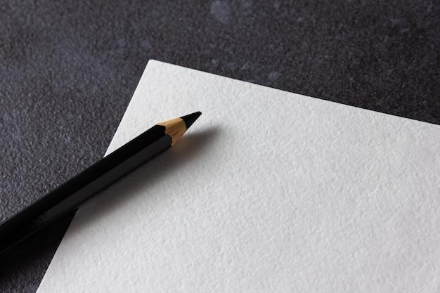 Papier akwarelowy a4 z czarnym ołówkiem na czarno. widok z góry.