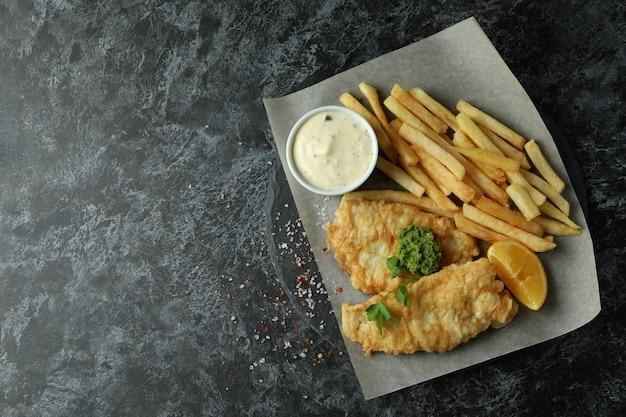 Papier do pieczenia ze smażoną rybą i frytkami na czarnym wędzonym stole