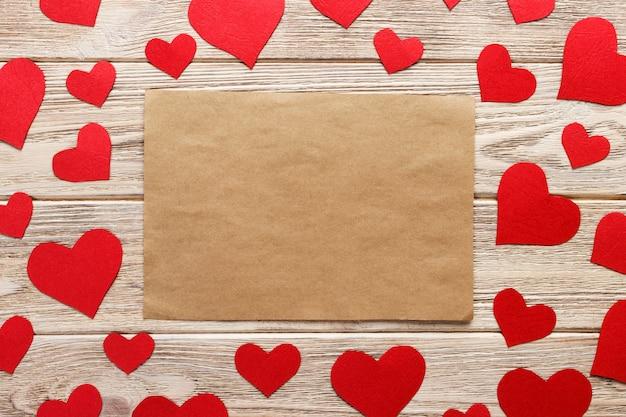 Papier do rękodzieła otoczony czerwonymi papierowymi sercami