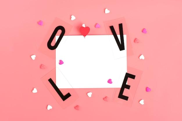 Papier do wiadomości, słowo miłość czarnych liter, cukierki w kształcie serca happy valentines day