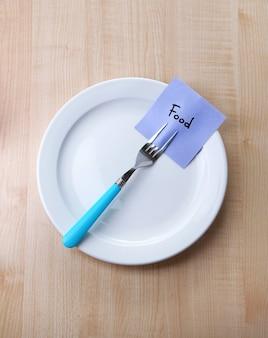 Papier firmowy z wiadomością przymocowaną do widelca, na talerzu, w kolorze drewna