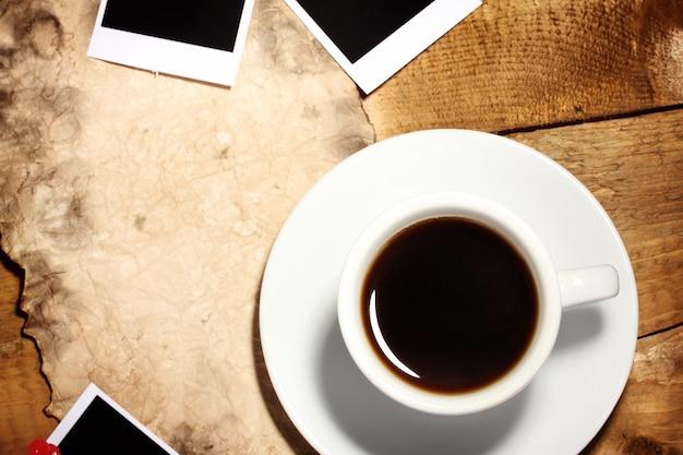 Papier fotograficzny z kawą i starym papierem na drewnianym tle