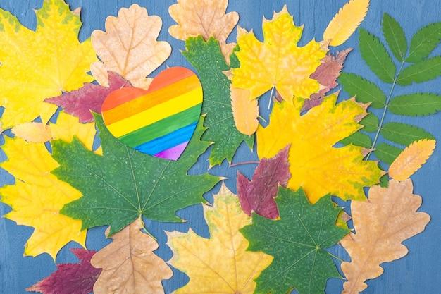 Papier jasny tęczowy serce na tle jesieni opadłych suchych kolorowych liści. jesienna koncepcja naturalnego tła. jesienna koncepcja lgbt