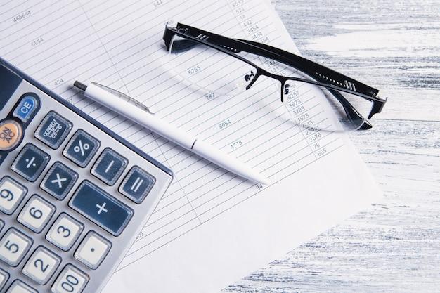 Papier, kalkulator i okulary na stole. koncepcja pulpitu