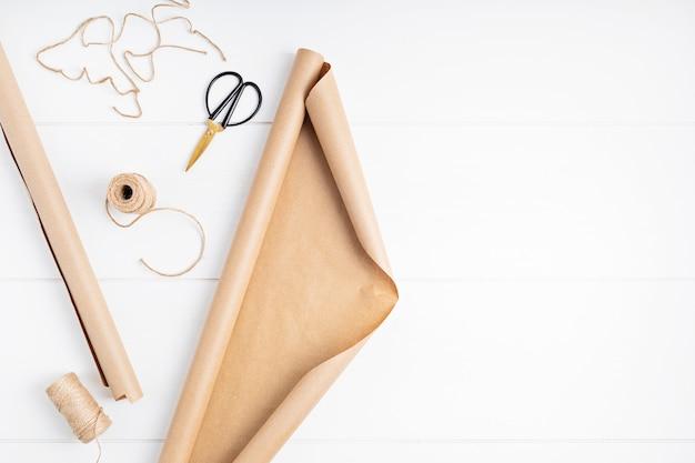 Papier kraft i akcesoria do pakowania prezentów i kwiatów. święta, boże narodzenie zrównoważony pomysł na prezenty. widok z góry, układ płaski