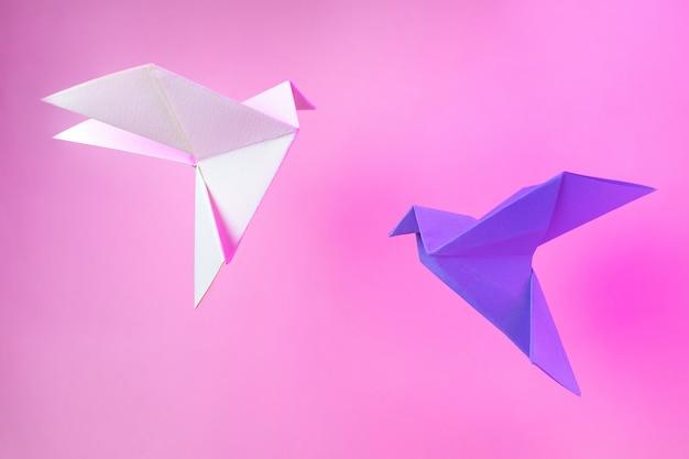 Papier origami dwa gołębie na pastelowym różu