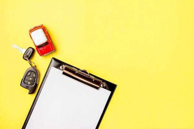 Papier puste z zabawkami czerwony samochód i klucze na żółtym tle. kontrola techniczna lub kredyt samochodowy.
