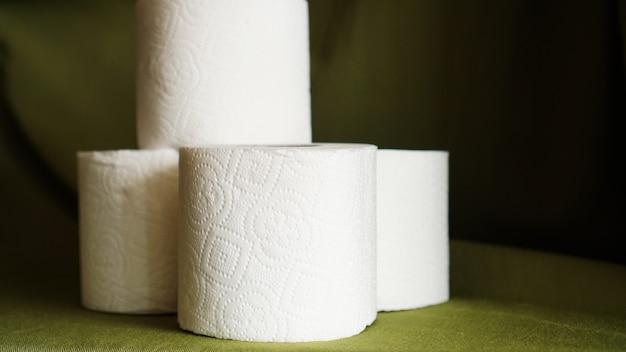 Papier toaletowy jest uważany za niezbędny przedmiot w czasie kryzysu. rolki tkanki na ciemnozielonym tle dla copyspace