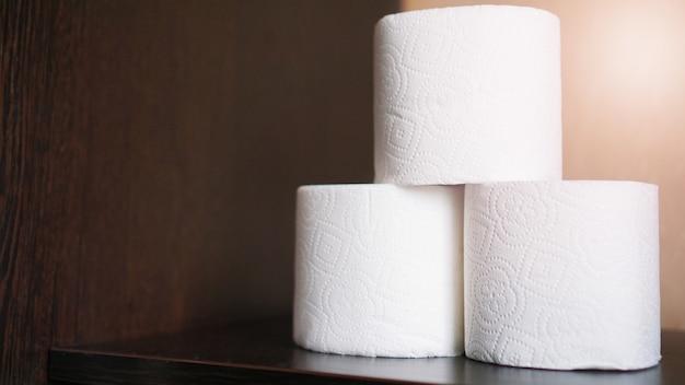 Papier toaletowy jest uważany za niezbędny przedmiot w czasie kryzysu. rolki tkanki na ciemnym tle dla copyspace