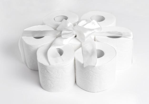 Papier toaletowy w prezencie z białą kokardką na białym tle