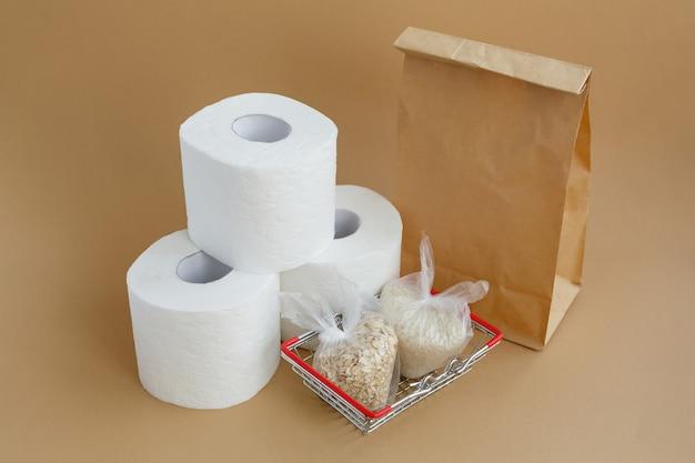 Papier toaletowy w torebkach papierowych i różne płatki zbożowe w małych plastikowych torebkach w koszyku spożywczym. ryż i płatki owsiane