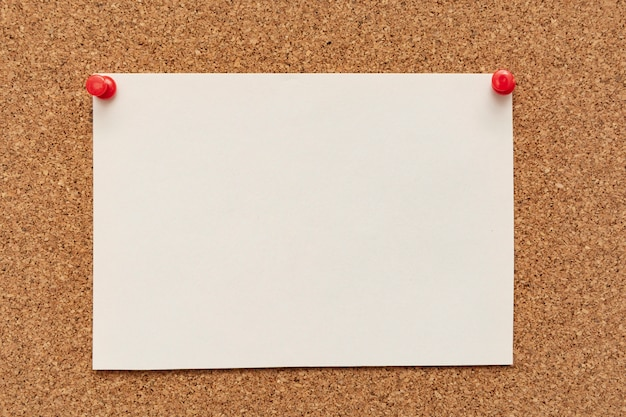 Papier w paski z pinezkami na tablicy korkowej