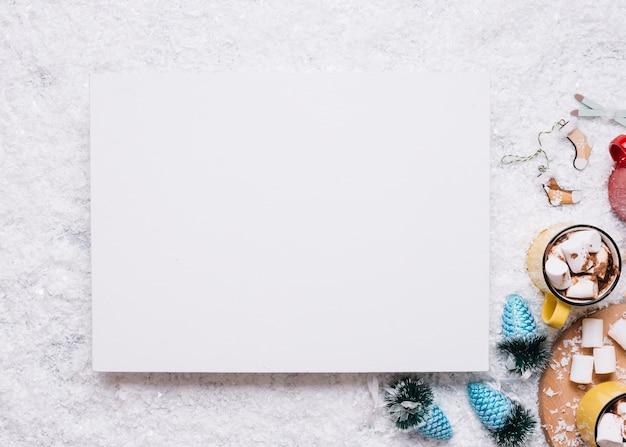 Papier w pobliżu kubki z pianki i świąteczne zabawki na śniegu