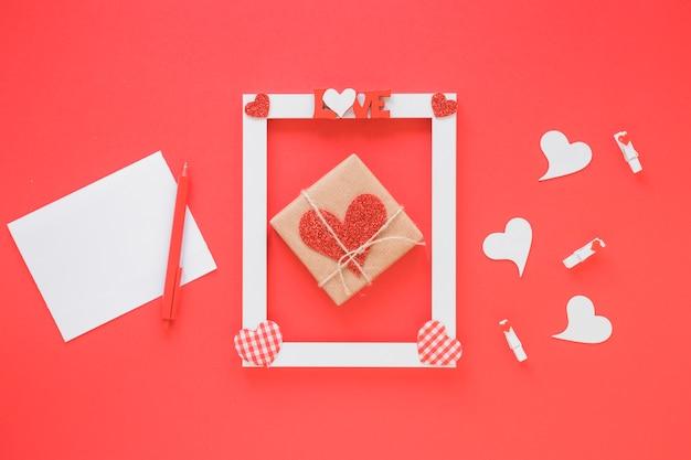 Papier w pobliżu ramki z symbolami miłości, teraźniejszości i serca