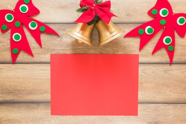 Papier w pobliżu świątecznych dzwonków i ozdobnych kokardek