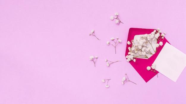 Papier z kopertą i kwiatem oddziałów na stole