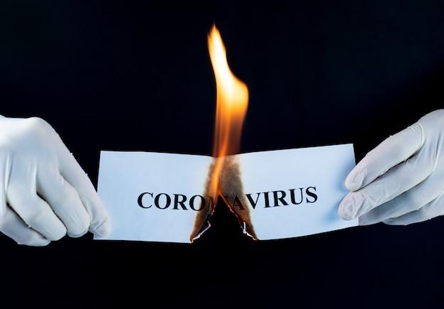 Papier z napisem koronawirus płonie w dłoni. koncepcja zakończenia pandemii koronawirusa.