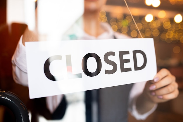 Papier z napisem zamkniętym wieszany przez młodą kelnerkę eleganckiej restauracji lub kawiarni stojącą za drzwiami pod koniec dnia pracy