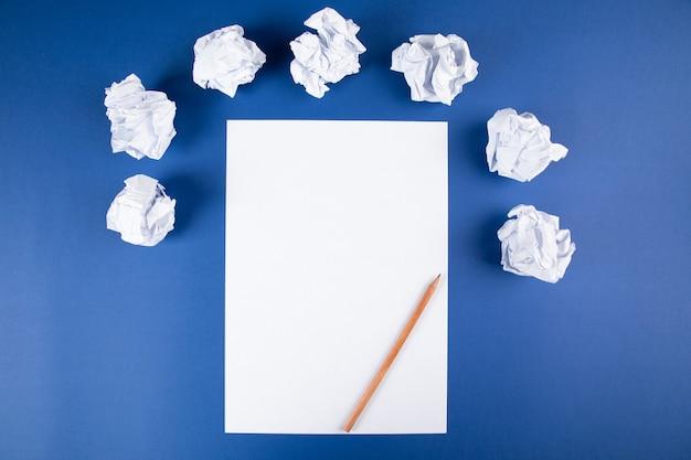 Papier z ołówkiem i zwitkami papierów na niebieskiej powierzchni