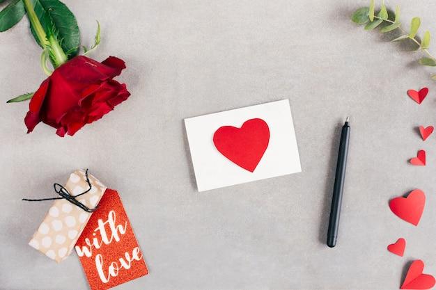Papier z serca w pobliżu tag, pióro i kwiat